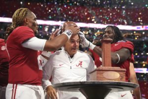 Sep 2, 2017; Atlanta, GA, USA; Alabama Crimson Tide quarterback Jalen Hurts (2) and Bo Scarbrough (9) put the old leather helmet on head coach Nick Saban after defeating the Florida State Seminoles 24-7 in the 2017 Kickoff Game at Mercedes-Benz Stadium. Mandatory Credit: Jason Getz-USA TODAY Sports