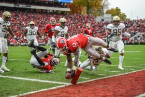 Nov 24, 2018; Athens, GA, USA; Georgia Bulldogs running back Elijah Holyfield (13) scores a touchdown over Georgia Tech Yellow Jackets defensive back Jaytlin Askew (33) during the first half at Sanford Stadium. Mandatory Credit: Dale Zanine-USA TODAY Sports